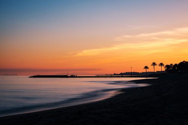 atardecer-playa-costa-sol-marbella-silueta-muelle-gibraltar_333245-20